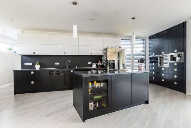 Černobílá kuchyň je optimálně rozvržena apropojena sjídelnou. Pracovní linku akuchyňský ostrov doplňuje solitérně umístěnýboční panel svestavěnými spotřebiči značky Whirlpool. Foto MIRO POCHYBA
