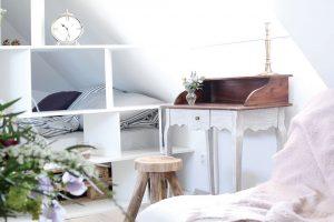 Pod střešní šikminou vznikl prostor ipro menší pracovní koutek se starobylým stolem a dřevěnou stoličkou. Foto HAUSMAUS