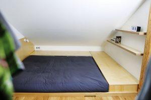 Nízké postele mají netypický odkladní aúložný prostor pod zešikmenou střechou. Foto TRAGA