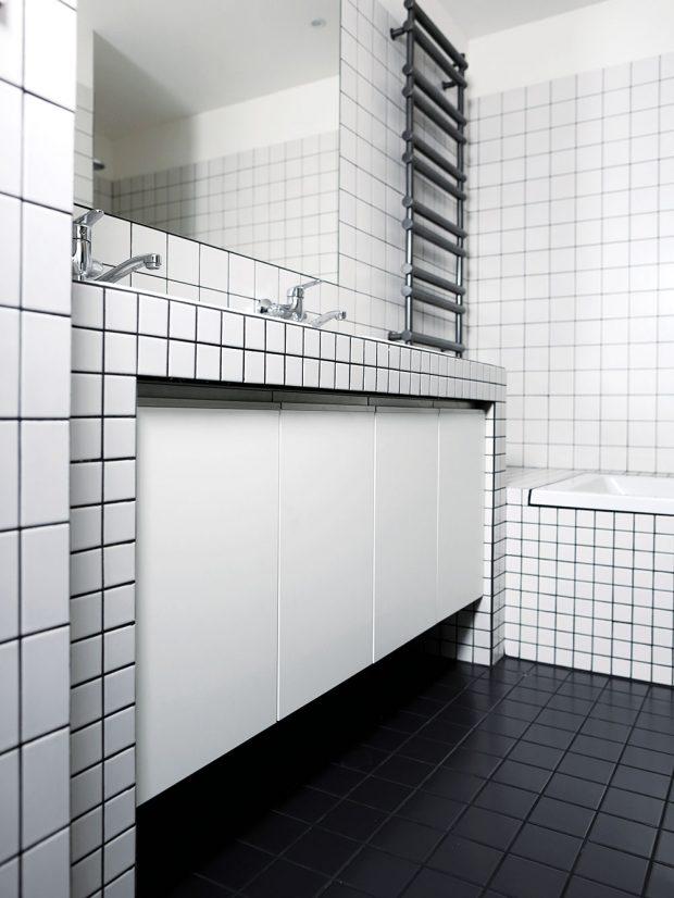 Koupelna je strohá místnost, ve které jsou kombinovány bílé kachličky s tmavou spárou a černé dlaždice. Foto TRAGA