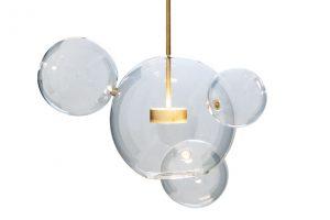 Závěsné svítidlo Bolles od Giopato aCoombes je vyrobené další technikou foukaného skla, typickou pro práci benátských sklářů, kteří přesně sestavovali skleněné koule pomocí mosazných spojek. Bubliny jsou umístěny tak, aby se navzájem dotýkaly avytvářely nekonečný shluk. FOTO MONOBRAND