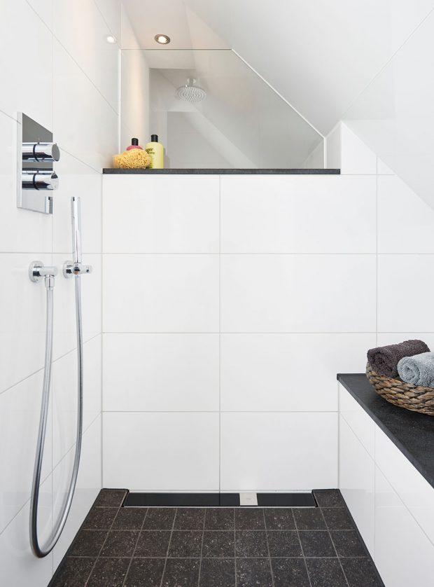 Sprchový kout typu walk-in poskytuje dostatečný prostor a volnost pohybu i v podkrovní koupelně se šikmým stropem. Takovéto řešení navíc koupelnu opticky otevře a díky bezprahovému přechodu ho investor ocení i ve vyšším věku. Jeho součástí je i praktická lavička. FOTO VIEGA, ROSE BENNINGHOFF