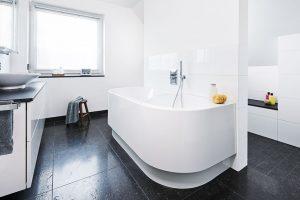 Dělicí předstěna místnost funkčně rozdělila a zároveň posloužila na instalaci vany zepředu a sprchy z druhé strany. V zadní části se potom nachází toaleta. FOTO VIEGA, ROSE BENNINGHOFF