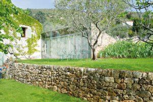 Sklo otevírá interiér do krajiny, tráva tvoří plynulý přechod mezi okolním terénem a přístavbou, kámen evokuje původní terasovité zídky. FOTO: HERVÉ ELIENA, V2COM