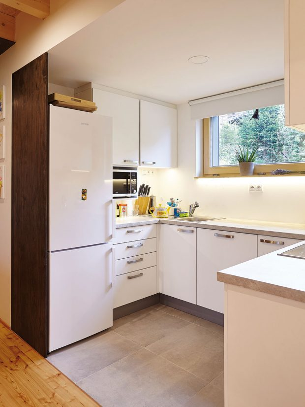 Minimalisticky řešená kuchyň navazuje na hlavní obytnou místnost. Oba prostory opticky odděluje snížený podhled a kontrast materiálů. FOTO: Jiří Princ