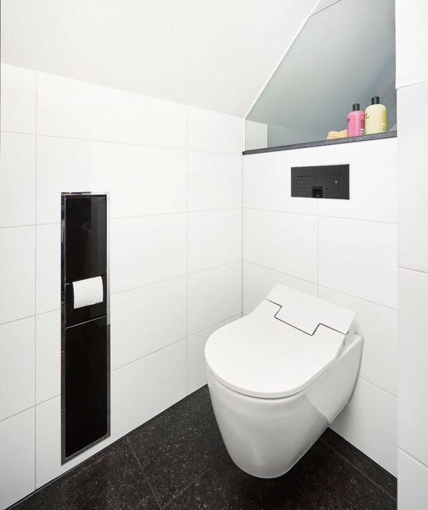Investor si přál, aby se i zařízení koupelny přizpůsobilo bílo-černé barevné kombinaci, která je příznačná pro celý interiér rodinného domu. Ta se objevuje i v prostoru toalety, kde se nachází černé splachovací WC tlačítko vsazené do bílého obkladu. FOTO VIEGA, ROSE BENNINGHOFF