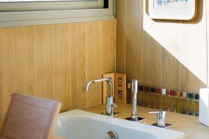 Z koupelny se nabízí výhled na travnatou terasu. Dřevo v interiéru plynule přechází do roviny kamenné zdi za posuvným oknem. FOTO: HERVÉ ELIENA, V2COM