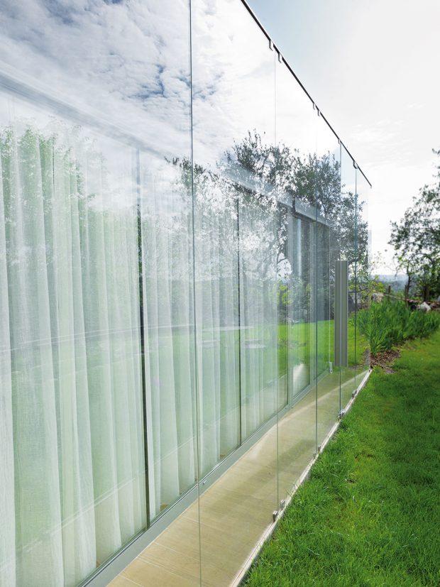 Ve skleněné fasádě se zrcadlí okolní příroda. Stěna zde není bariérou, ale prvkem spojujícím exteriér a interiér v jeden velkorysý celek. FOTO: HERVÉ ELIENA, V2COM