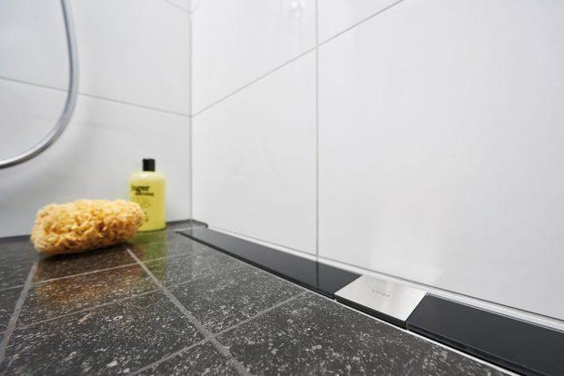 5 Sprchový žlab je harmonicky začleněn do podlahy. Projektant v tomto případě zvolil odtok ke stěně a rám z nerezavějící oceli s designovým roštem z černého bezpečnostního skla. FOTO VIEGA, ROSE BENNINGHOFF