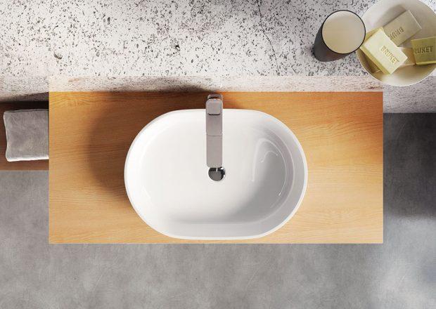 Umyvadlo na desku Moon je vyrobené z litého mramoru. Posadit ho můžete například na desku z dřevěné dýhy, která v kombinaci s bílou barvou mramoru působí útulně. Navíc je hloubkově impregnovaná, takže odolá vlhkému prostředí. FOTO RAVAK