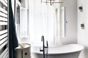 Koupelna s výhledem do zahrady představuje jedno z Moničiných nejoblíbenějších míst. Kombinace minimalismu, mramorové mozaiky, orientálního zrcadla a lustru od Ay illuminate je velmi příjemná. FOTO LE PATIO/PETR KARŠULÍN