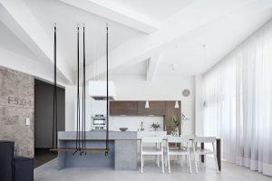 Tenká deska procházející ostrůvkem tvoří i jídelní stůl, který je doplněný bílými židlemi Merano od firmy TON.FOTO BOYSPLAYNICE