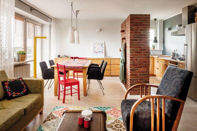 KUCHYNI od obývacího pokoje opticky odděluje široký sloup. Místy z něj vyčnívají cihly, které slouží jako poličky na suvenýry a drobnosti.