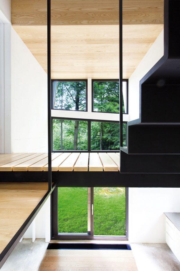 Aby byl uvnitř chaty dostatek světla, nenajdeme zde mnoho zdí. Místo kryté chodby proto na schodiště v patře navazuje dřevěná lávka, po které se lze dostat do pokoje. FOTO FRANCIS PELLETIER
