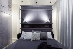 V tmavé ložnici je výrazným prvkem rozměrná postel s vysokým čelem, umístěná doprostřed místnosti, za ní se nachází prostor pro šatnu. FOTO BOYSPLAYNICE