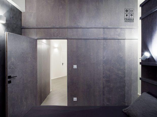 Šatna a obložení stěny v ložnici, ve kterém je schovaná technická místnost s pračkou a sušičkou, má evokovat přepravní kontejnery.FOTO BOYSPLAYNICE