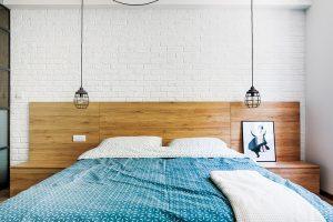 Osvětlení u postele tvoří ze stropu spuštěná kovová svítidla. Vypínače jsou zapuštěny do čela postele.