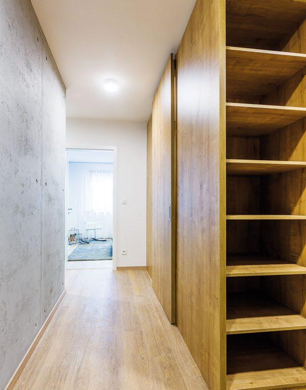 Prakticky istylově. Zvelkorysé vstupní haly odděluje vložená dřevěná konstrukce praktický šatník amalé zádveří smístem na přezutí aodložení kabátů. Když se zavřou posuvné dveře na celou výšku místnosti, zůstane jen příjemně působící elegantní dřevěná stěna. FOTO MIRO POCHYBA