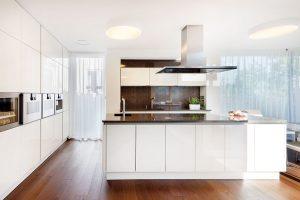 Dvířka kuchyňské linky jsou zlakované MDF, bílou doplňuje kámen pracovní desky istolu. FOTO JAROSLAV HEJZLAR