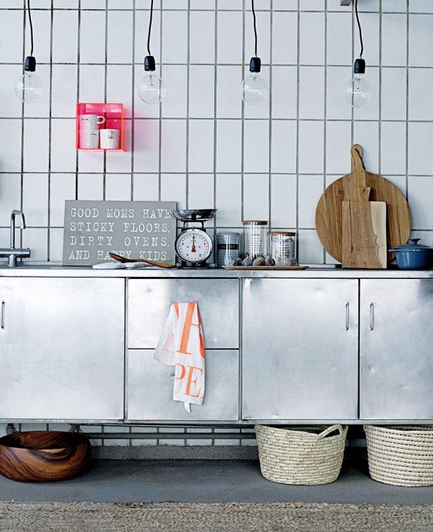 Mezi jeden z kuchyňských trendů patří i ocelová dvířka skříněk. Krásně vyniknou v kombinaci s jednoduchými obdélníkovými dlaždicemi, poskládanými neobvykle na výšku. FOTO BLOOMINGVILLE