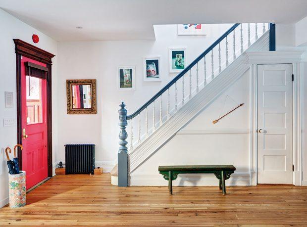 Dominantní červené vstupní dveře jsou přímo naproti schodům. Právě ty, imnoho dalších věcí vinteriéru, například zelenou lavičku, si majitelé nechali zrenovovat. FOTO FRANCIS DZIKOWSKI