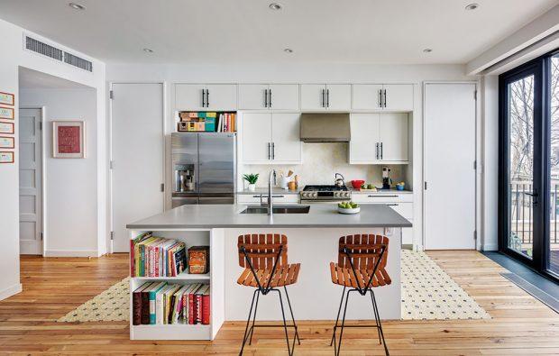 Na knihy narazíte po celém domě, ivkuchyni, která je oproti zbytku interiéru vcelku střídmě zařízená. Neutrální bílou linku ale příjemně doplňují dřevěné barové židličky. FOTO FRANCIS DZIKOWSKI