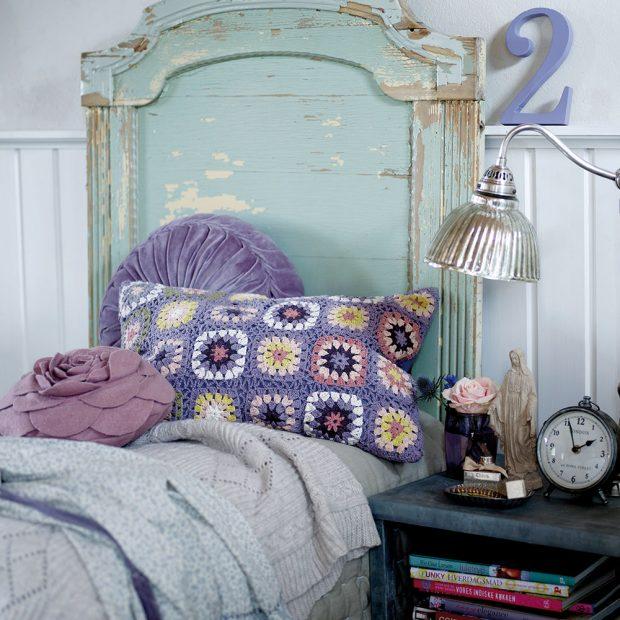 Lehce rustikálního vzhledu ve stylu Provence docílíte také díky oprýskanému čelu postele asvětle fialových polštářů. Na noční stolek si nezapomeňte dát pár starožitných dekorací. FOTO BLOOMINGVILLE