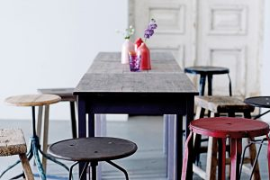 Máte-li rádi industriální styl, není problém ho přenést ani do jídelny. Drsnějšího vzhledu docílíte pomocí kovových stoliček i stolu s hrubou neopracovanou deskou. Spoustu věcí lze pořídit z druhé ruky nebo v bazaru. Nad jídelní stůl si zavěste ještě veliký kovový lustr. FOTO BLOOMINGVILLE