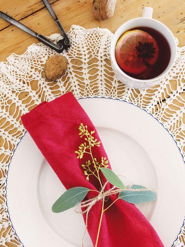 Vánoční prostírku nemusíte připravovat jen na štědrovečerní stůl – proč si neozvláštnit večeři spřáteli hezky prostřeným stolem. Idrobná snítka položená na ubrousku každého zhostů dostatečně oživí slavnostní tabuli. FOTO KVĚTERIE
