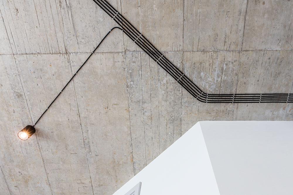 Po vstupu do obývacího pokoje zaujme betonový strop avedení elektrických kabelů ke světlům. Dříve se kabely schovávaly pod omítku, dnes je architekti rádi nechávají přiznané. Byt působí lehce industriálním dojmem, který koresponduje sdomem alokalitou. FOTO FRANTIŠEK GÉLA, FABIÁN FRONČEK