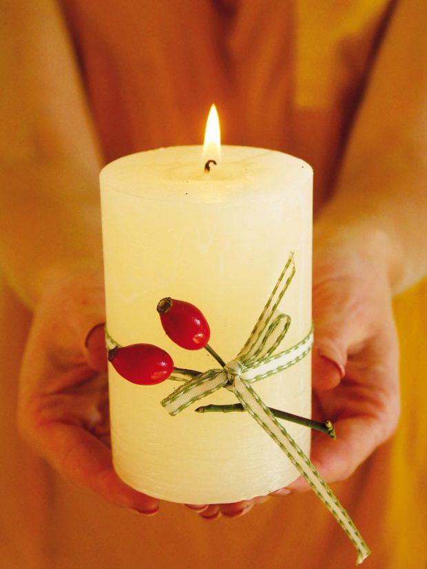 Vlastnoručně nazdobená svíčka může zdobit váš byt, nebo jí můžete obdarovat své blízké. Jednoduchou svíčku stačí omotat stuhou či provázkem apřidat kousek šípku, větvičky nebo třeba hvězdičku koriandru. FOTO KVĚTERIE