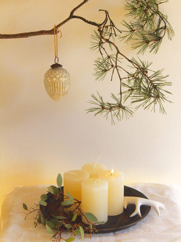Adventní svícen nemusí být vždycky vpodobě kulatého jehličnanového věnce. Minimalistickou formou adventního svícnu může být iplechový tácek sklasicky čtyřmi svíčkami. Tácek lze dozdobit buď tradičnější větvičkou jedle (Abies), nebo například eukalyptem (Eucalyptus), popřípadě lze dekoraci vprůběhu adventu stále pozměňovat či dozdobovat. FOTO KVĚTERIE
