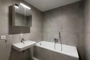Jednoduché čtvercové obklady šedé barvy pokrývají vkoupelně podlahu, stěny ivanu. Nenápadný vzhled místnosti doplňuje celkový charakter bytu. FOTO FRANTIŠEK GÉLA, FABIÁN FRONČEK