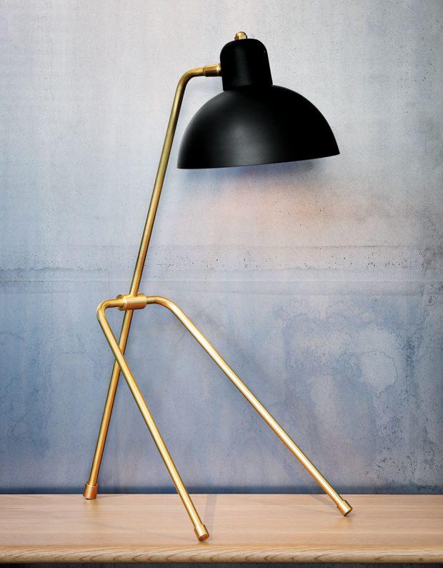Stolní lampička Grue (50,2 x 22,9 cm) zkolekce Waldorf kombinuje otevřené půlkulové stínidlo scylindrickým krytem zásuvky. Praktické otočné stínidlo je umístěno na stabilní minimalistické trojnožce.