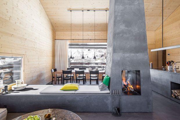 Dominantou je betonový krb vhlavní části domu. Praktická lavice, která navazuje na krb, slouží jako odpočinkový prostor azároveň opticky rozděluje místnost na několik zón – jídelní sprostorným stolem akuchyní ana druhé straně relaxační spohodlným gaučem. FOTO CHRISTIAN SCHAULIN