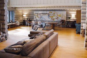 Dispozičně je srub rozdělen na hlavní denní místnost, která zabírá 80 % plochy domu, adalší místnosti smnohem menší rozlohou. Ani zde není žádný kus nábytku zbytečný – pro spokojený život postačí pohovka, chaise-lounge, jídelní stůl aodpovídající počet židlí, případně nevelká komoda. FOTO KAISA SIRÉN