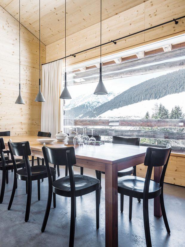 Udlouhého jídelního stolu zvlašského dřeva, vyrobeného na zakázku, se schází rodina nejen při jídle, ale ipři večerních společenských hrách. Fascinující výhled do okolních hor, který nabízí velká okna, je však tou největší zábavou. FOTO CHRISTIAN SCHAULIN