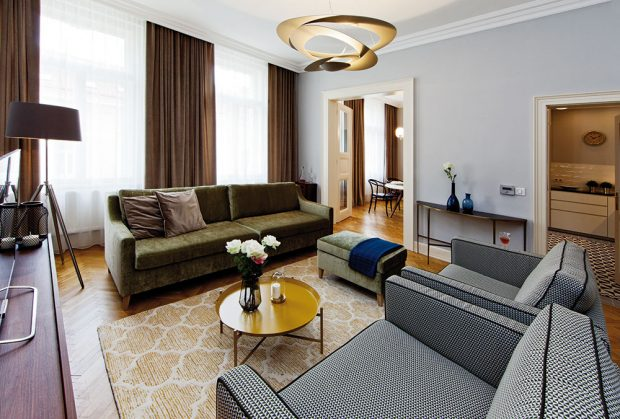 Obývací část je vybavena sametovým gaučem isametovými závěsy. Geometrický vzorek potahů křesel barevně ladí sčernobílou podlahou vkuchyni. FOTO JIŘÍ VANĚK