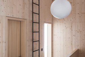 Mezi pokoji vede úzký žebřík až kbývalému seníku, který připomíná cestu ztemnoty ke světlu. Askutečně, vprvním patře jsou díky okýnku překvapivě jasné prostory. FOTO CHRISTIAN SCHAULIN