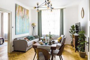 """Centrem obývacího pokoje je dřevěný jídelní stůl, který doplňují známé židličky z firmy Tatra nábytek Pravenec (vyráběly se tu asi v letech 1960–1970). """"Umístění stolu si vlastně prostor určil sám,"""" tvrdí majitelka. FOTO NORA A JAKUB ČAPRNKOVI"""
