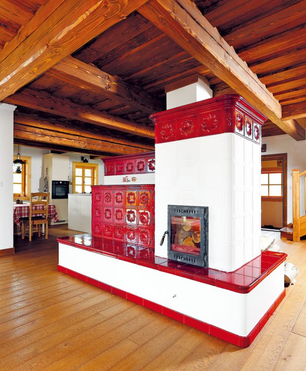 Jedna zmožností pro tepelný komfort ve dřevostavbě: zde se snoubí historická zkušenost svelkým prostorem. Kamna tvoří základ vytápění celodřevěné chalupy. Vposchodí je navíc elektrické podlahové astěnové vytápění (podlahové vkoupelnách, stěnové vpokojích). FOTO DANO VESELSKÝ