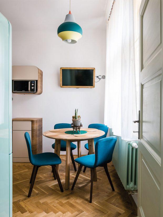 Součástí kuchyně je isympatický jídelní koutek smodrými pohodlnými židlemi aretro lampou vpodobném odstínu. Majitelé však nejraději jedí vprostorném obývacím pokoji. FOTO NORA A JAKUB ČAPRNKOVI