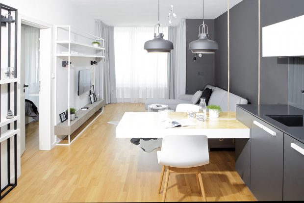 Úzký prostor opticky zvětšují barvy. Stěny v bytě jsou vymalované bílou a tmavě šedou barvou, ve stejném odstínu je provedena také kuchyňská linka. FOTO ROBERT ŽÁKOVIČ