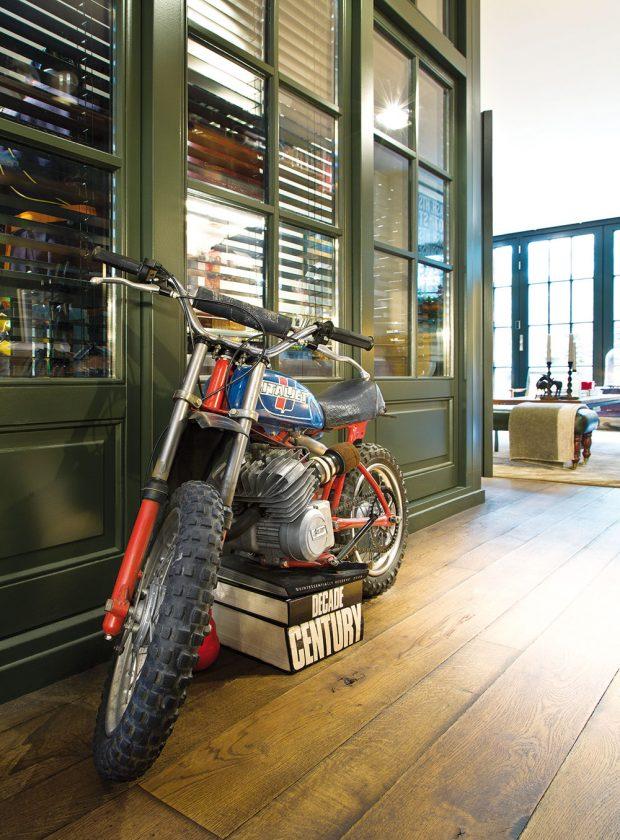 Nebojte se, nešálí vás zrak. Vedle stěny do pracovny je na podstavci zknih opravdu umístěna retro motorka značky Italjet. FOTO WESTWING HOME&LIVING