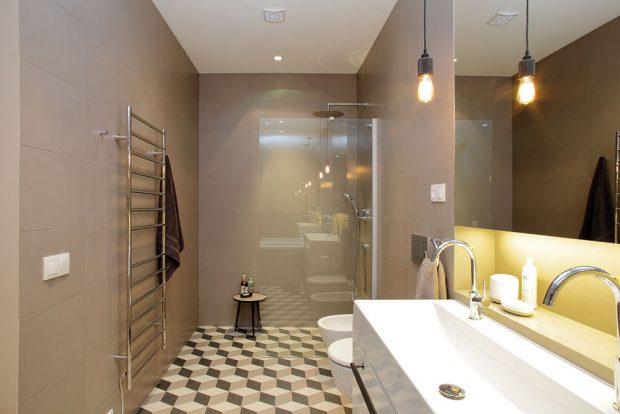 Koupelně vládnou přírodní tóny avelkoformátová dlažba, která opticky zvětší malý prostor. Díky zrcadlům avhodnému osvětlení působí koupelna prostorně. FOTO ROBERT ŽÁKOVIČ