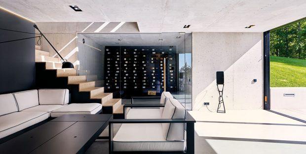 Zvelkoryse řešeného obývacího pokoje se vchází do patra, kde jsou ložnice. Celý prostor je jednoduše řešený anechává vyniknout kráse okolní přírody. Spodní podlaží apřízemí vily tvoří dvouvrstvá vyztužená betonová konstrukce sinteligentní izolací, která umožňuje betonový povrch přiznat zevnitř izvenku. FOTO MĀRIS LOČMELIS AINGUS BAJĀRS