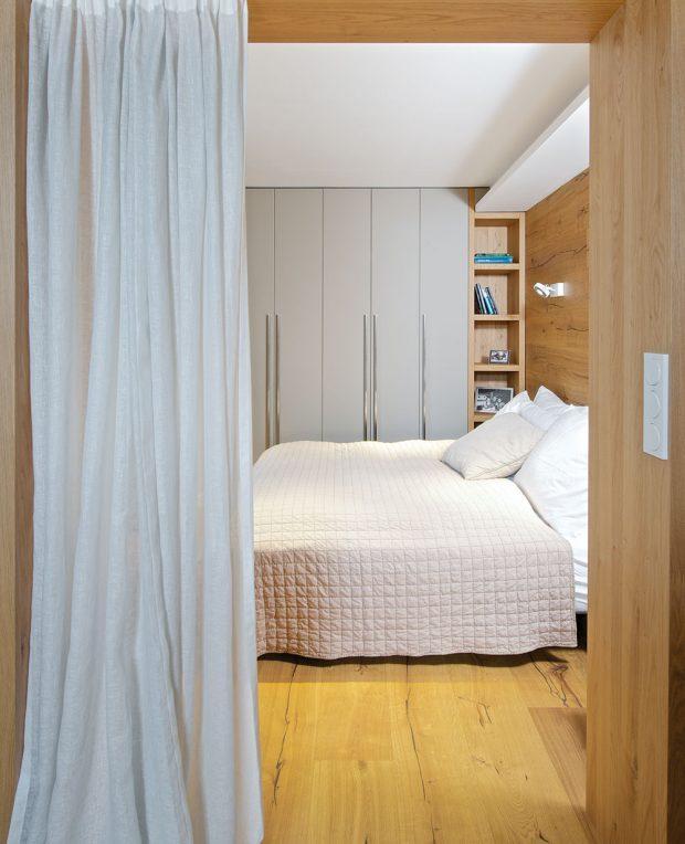Ložnice je od obývacího pokoje oddělena závěsem a opticky opět masivním obložením. FOTO IVETA KOPICOVÁ