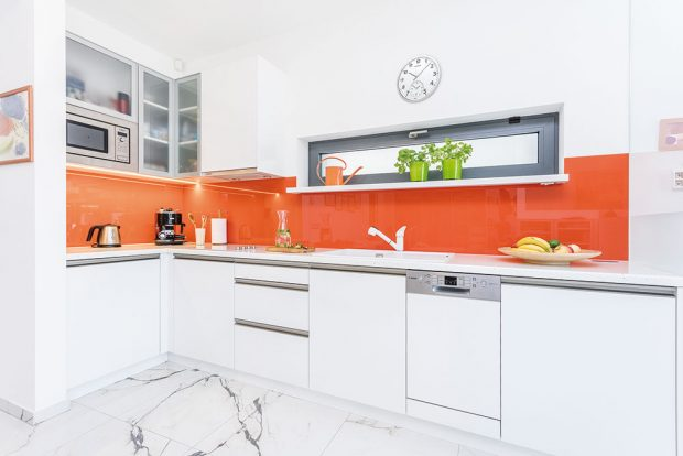Bílou, na míru vyrobenou kuchyňskou sestavu doplňuje oranžové lakované sklo. FOTO FH STUDIO