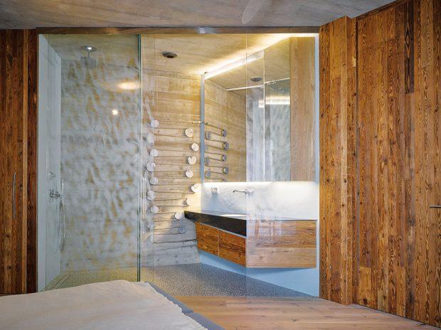 Zajímavým prvkem koupelny oddělené avlastně propojené složnicí skleněnou stěnou je lité kovové topné těleso, jehož tvar je odvozen zdřevěných špalíků ajde tak daleko, že přiznává iletokruhy. FOTO FILIP ŠLAPAL