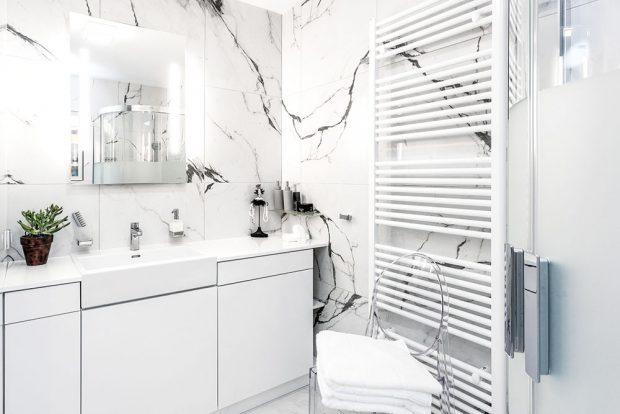 Mramor se opakuje i v koupelně, tentokrát i na stěnách. Opět je doplněný čistě bílým nábytkem. FOTO FH STUDIO